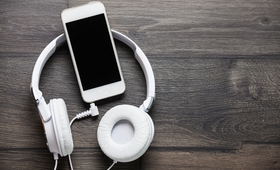 White headphones and smart phone on wooden table